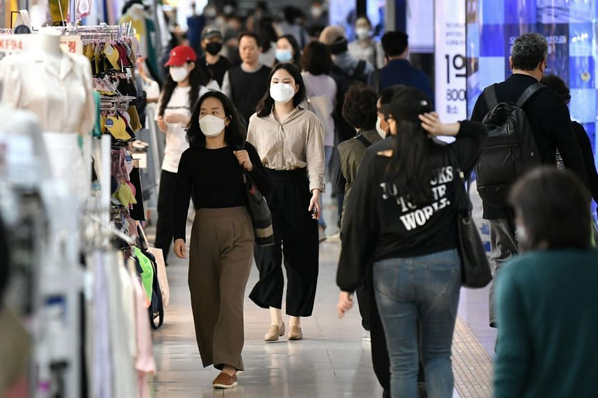 People wearing face masks walk through an underground shopping area in Seoul, on May 6, 2020.