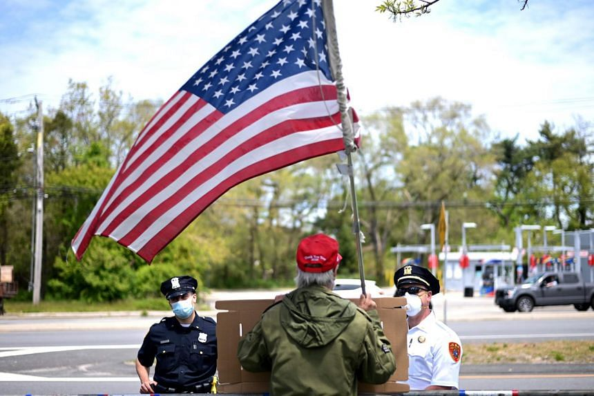 """A protestor waves a US flag as they attend an """"Open New York"""" Rally, on May 14, 2020."""