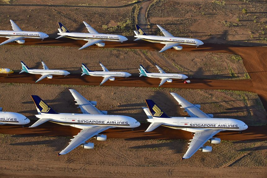 Airplanes belonging to Singapore Airlines (SIA) as well as its subsidiaries SilkAir and Scoot are parked at a storage facility in Alice Springs, Australia, as the coronavirus pandemic causes a steep drop in air travel. SIA reported a full-year loss i