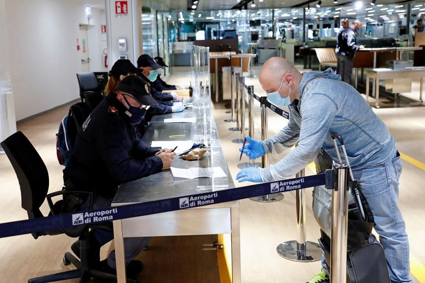 A police officer checks a traveller's self-certification at the Fiumicino airport in Rome on May 6, 2020.