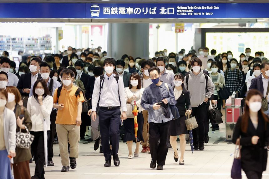 Commuters wearing protective face masks at a train station in Fukuoka yesterday, a day after the Japanese government announced the lifting of the state of emergency in 39 of 47 prefectures. The 39 prefectures account for about 55 per cent of Japan's