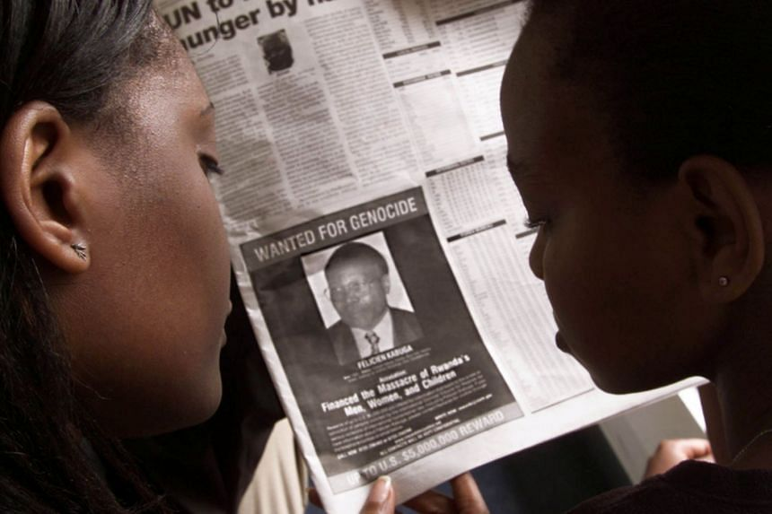 Readers in Nairobi look at a newspaper report dated June 12, 2002, carrying a photograph of Felicien Kabuga.