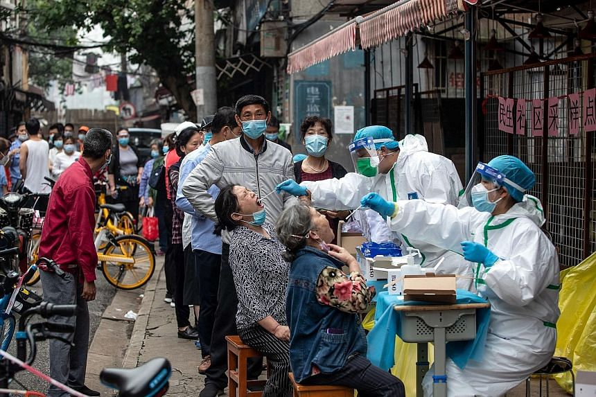 Medical workers taking swab samples from residents for Covid-19 testing in a street in Wuhan on Friday. Safety has become a hot topic on social media among the 11 million residents of Wuhan, as well as among people crowding the test centres, who expr