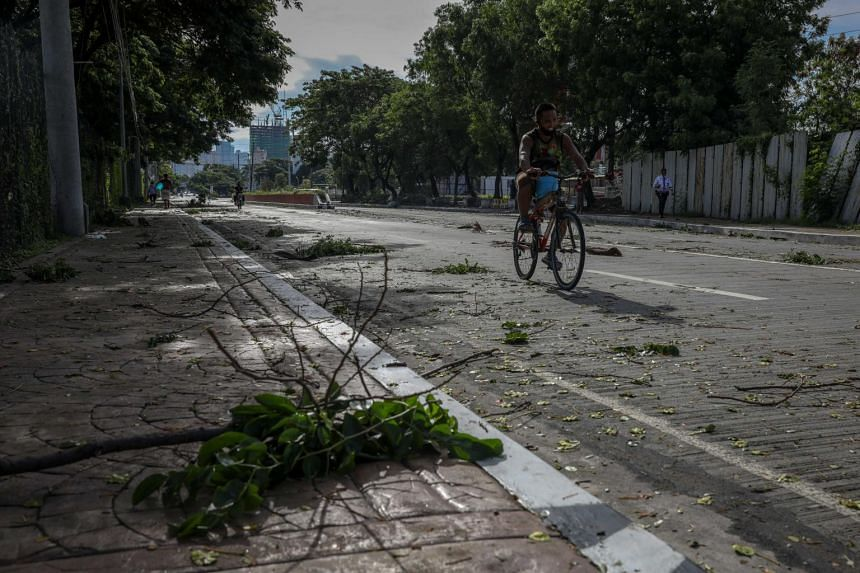 A man cycles along scattered tree branches in Pasay city, south of Manila, Philippines, on May 16, 2020.