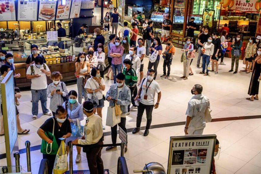 People stand in line to enter the Siam Paragon shopping mall in Bangkok on May 17, 2020.