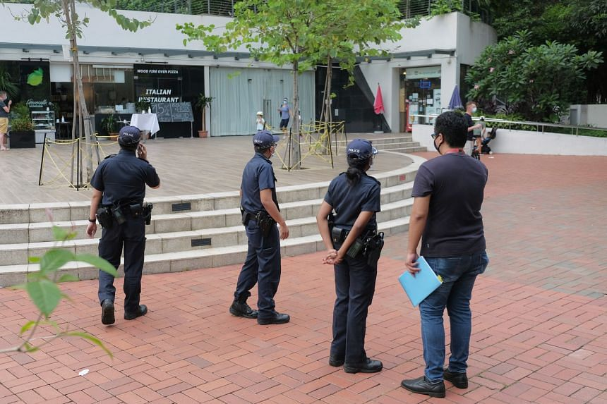 Police (above) patrolling in the Robertson Quay area yesterday. The URA ban on alcohol takeaways came after a Facebook post showing photos of people failing to stay at least 1m from one another on Saturday (left) in the waterfront area went viral.