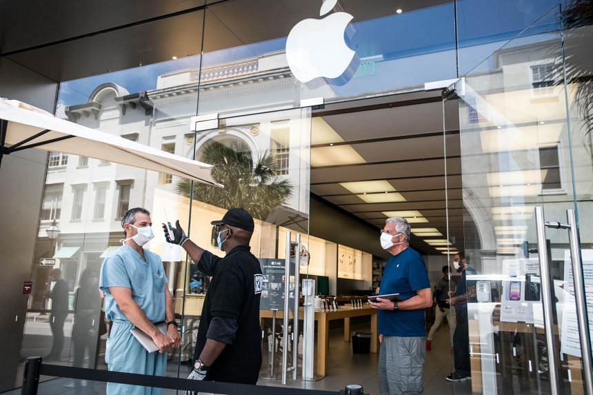 A security guard takes the temperature of a customer outside the Apple Store, on May 13, 2020, in Charleston, South Carolina.