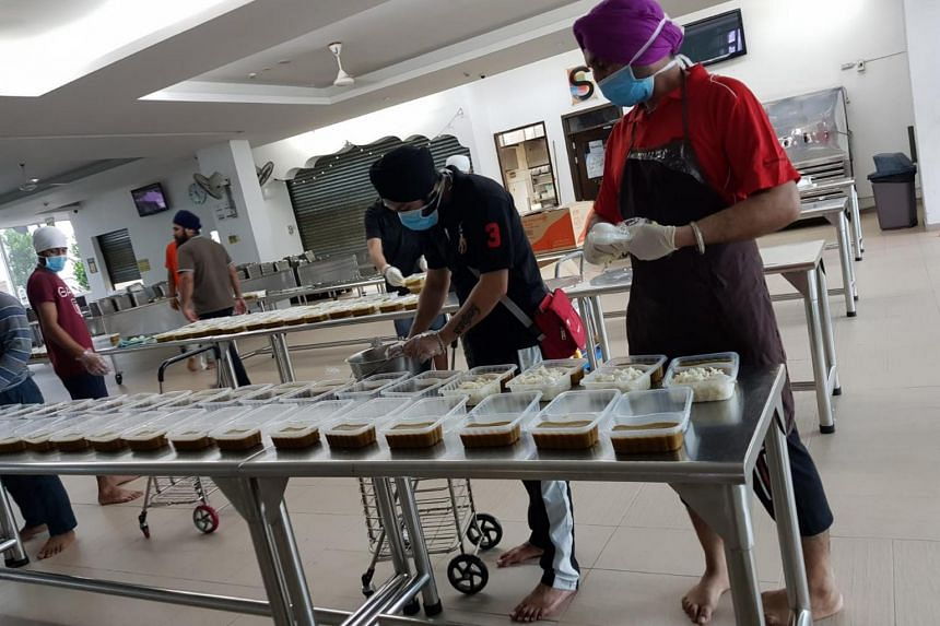 Volunteers packing lentil curry and rice at Central Sikh Temple.