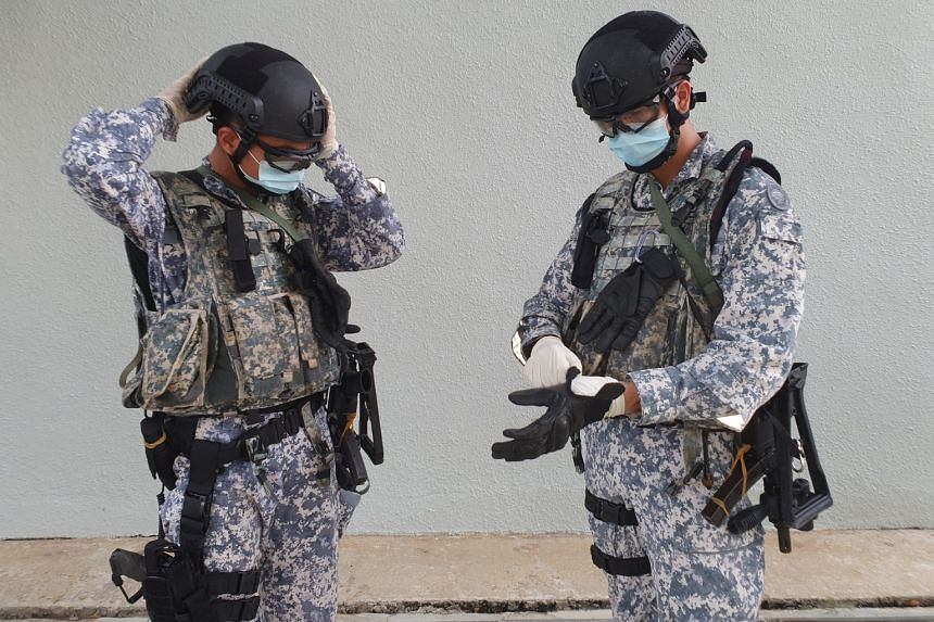 Above: Private Nigel Lim (left), 22, putting on personal protective equipment that includes a mask, goggles and latex gloves. Left: An Accompanying Sea Security Team operator speaking to a crew member on board a merchant ship during a recent operatio