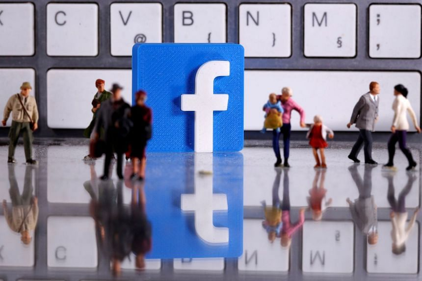 A 3D printed Facebook logo is placed among figures of people in front of a keyboard in a photo illustration.