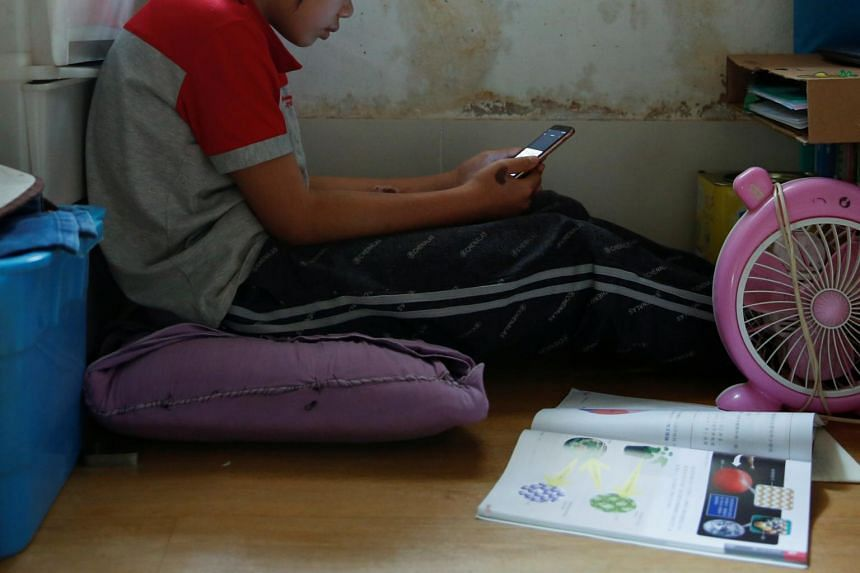 A student attends an online class with a smartphone at home in Hong Kong on March 16, 2020.