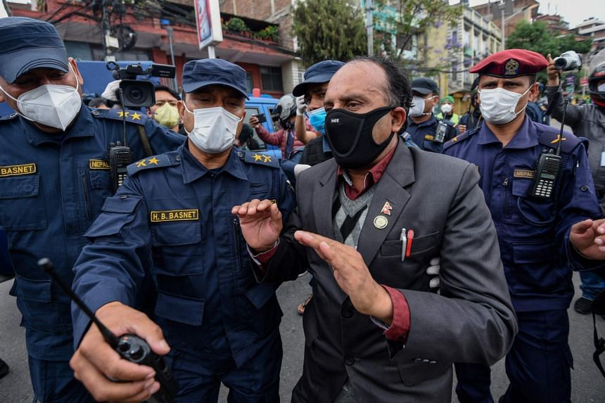 Police detain a demonstrator during a protest, in Kathmandu, Nepal, on May 10, 2020.