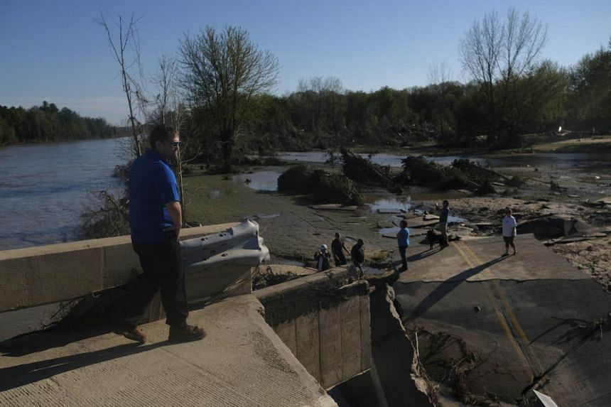 Residents explore what remains of the West Curtis Road bridge which was swept away following extreme flooding throughout central Michigan on May 20, 2020.
