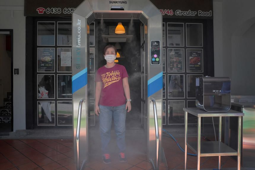 Waitress Erlinda Chia, 45, demonstrating the use of a disinfection tunnel at Hello Korean BBQ restaurant. Two firms providing such tunnels here say they use non-toxic disinfectants which are safe for people.