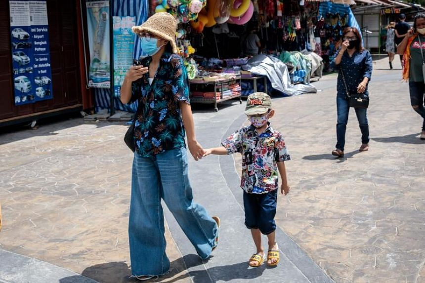 A woman and a child walking past shops in Thailand's Hua Hin beach area on May 19, 2020.