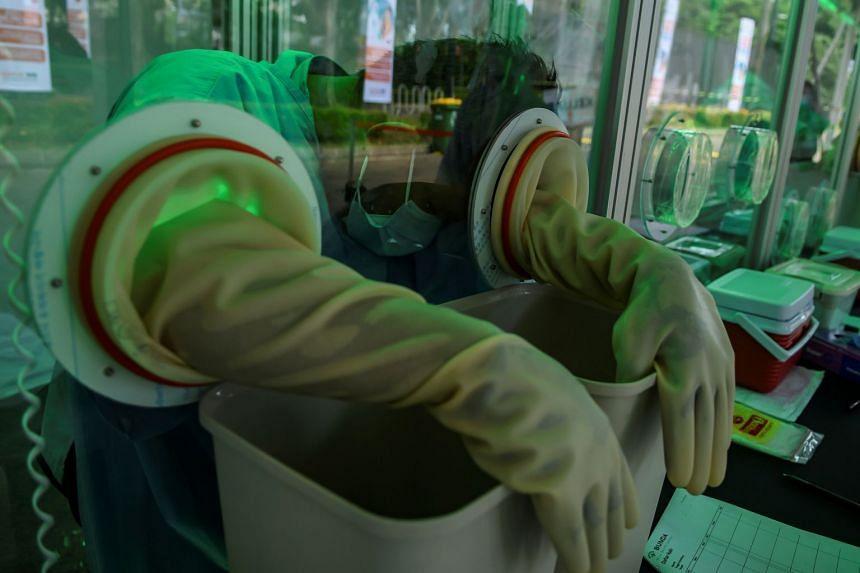 A medical staff member waits to take a coronavirus swab sample in Jakarta, Indonesia, May 20, 2020.