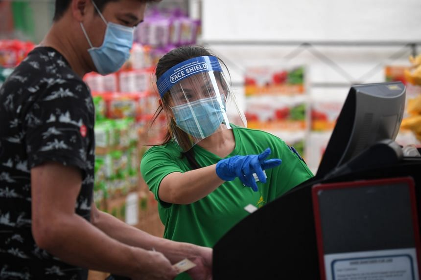 A cashier wearing a mask under a face shield at Sheng Siong supermarket on May 13, 2020.