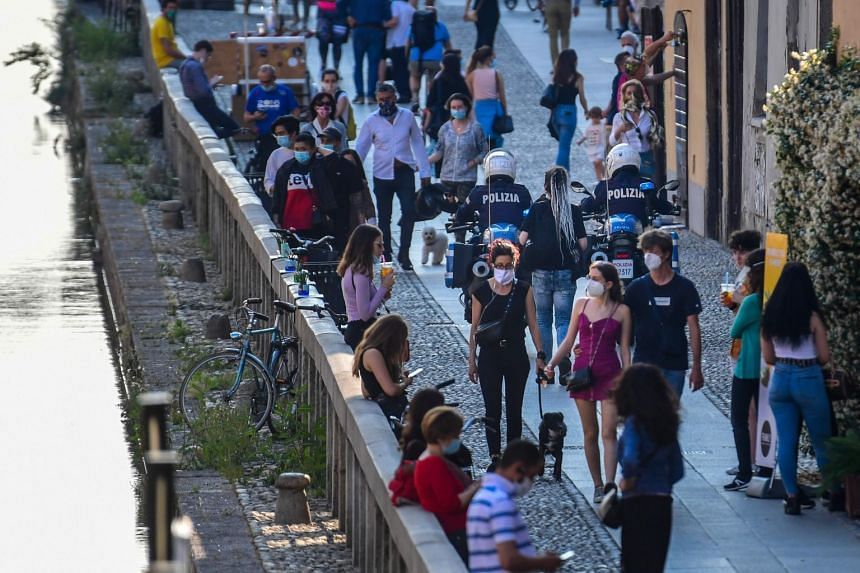 Police officers patrols on motorbikes as people stroll and have a drink along a canal in the Navigli district of Milan on May 21, 2020.