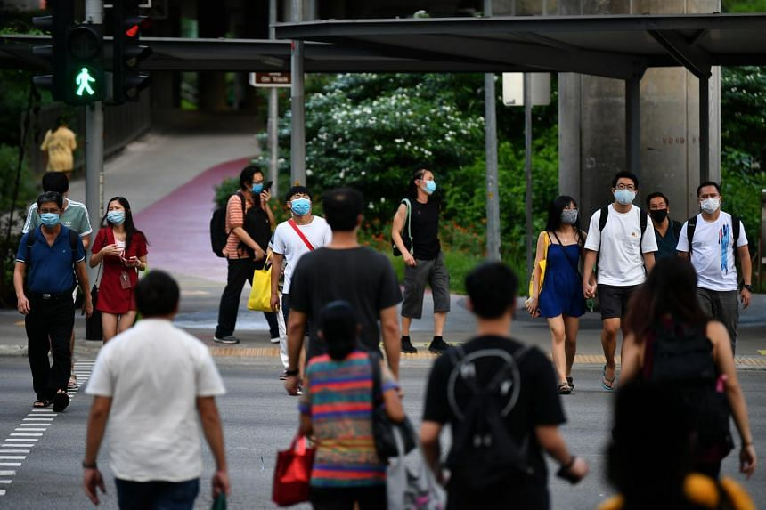 People wearing face masks cross the road outside Ang Mo Kio MRT station on May 15, 2020.