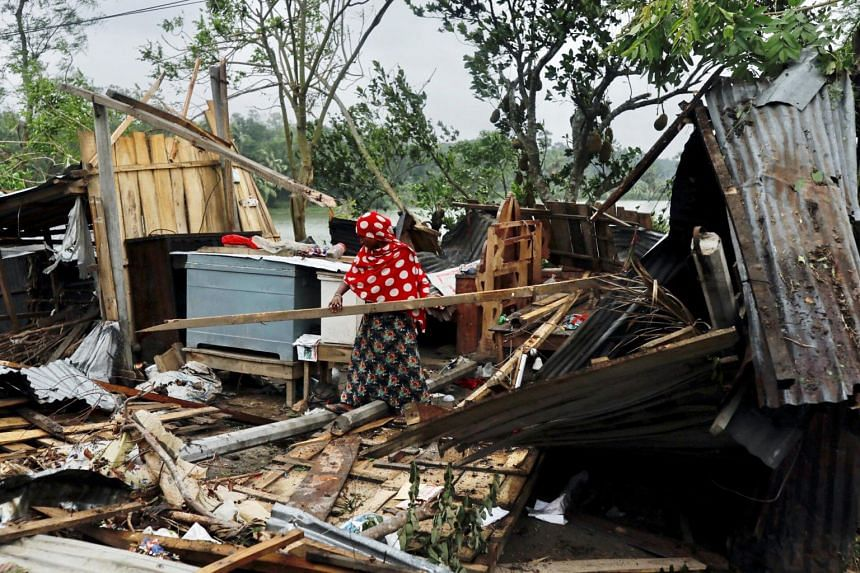 A woman clears her house that was demolished by Cyclone Amphan in Satkhira, Bangladesh, on May 21, 2020.