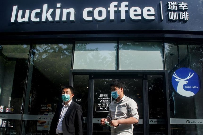 People walk out of a branch of Luckin coffee in Beijing on May 20, 2020.