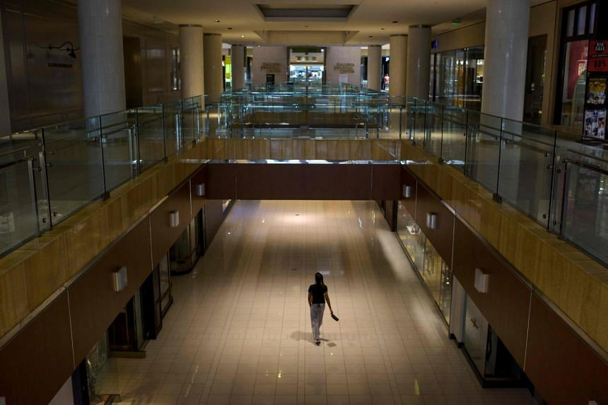 Shoppers walk around a shopping centre in Houston on May 1, 2020.