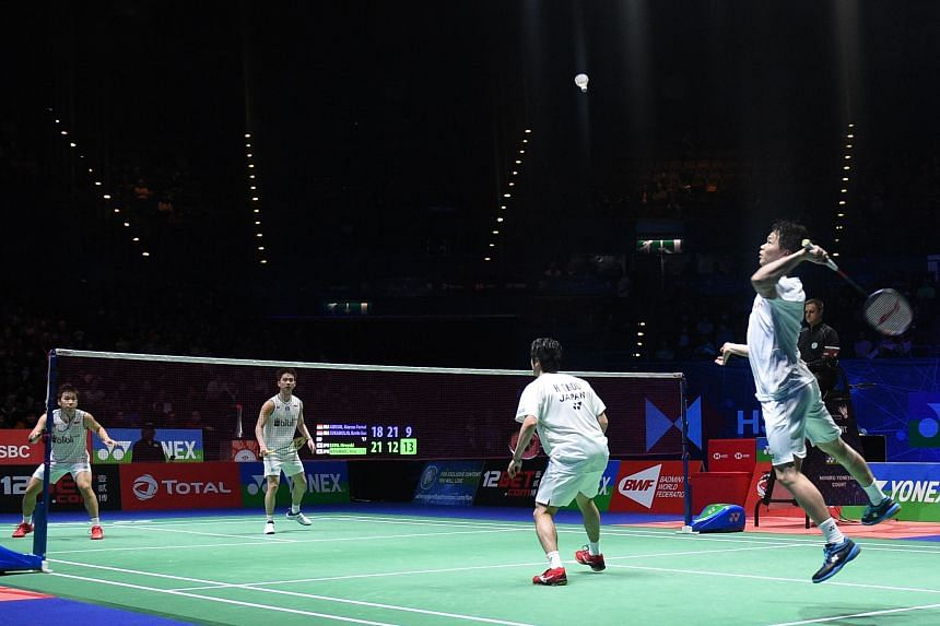 Japan's Hiroyuki Endo and Yuta Watanabe (right) return against Indonesia's Marcus Fernaldi Gideon and Kevin Sanjaya Sukamuljo (unseen) in Birmingham, England, on March 15, 2020.