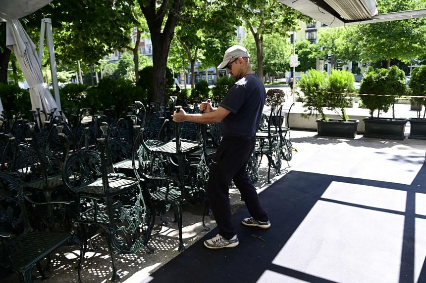 Employees prepare the outdoor seating area of a restaurant in Madrid on May 21, 2020.