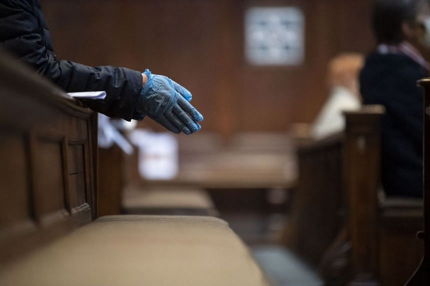 A believer wears protective gloves during a church service in Munich, Germany, on May 16, 2020.
