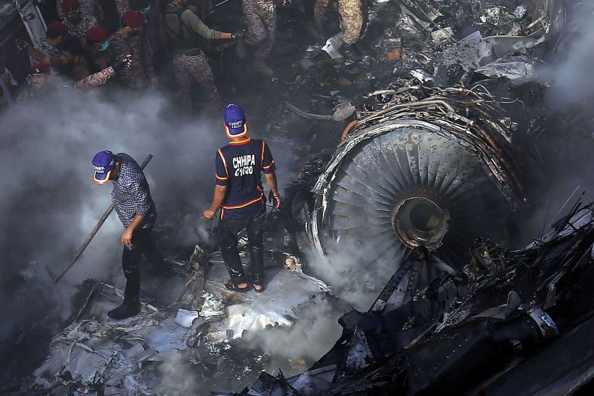 Rescue workers search for bodies or survivors amid the wreckage.