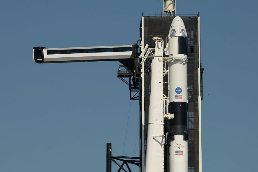 The crew access arm is swung into position to a SpaceX Falcon 9 rocket with the company's Crew Dragon spacecraft onboard.