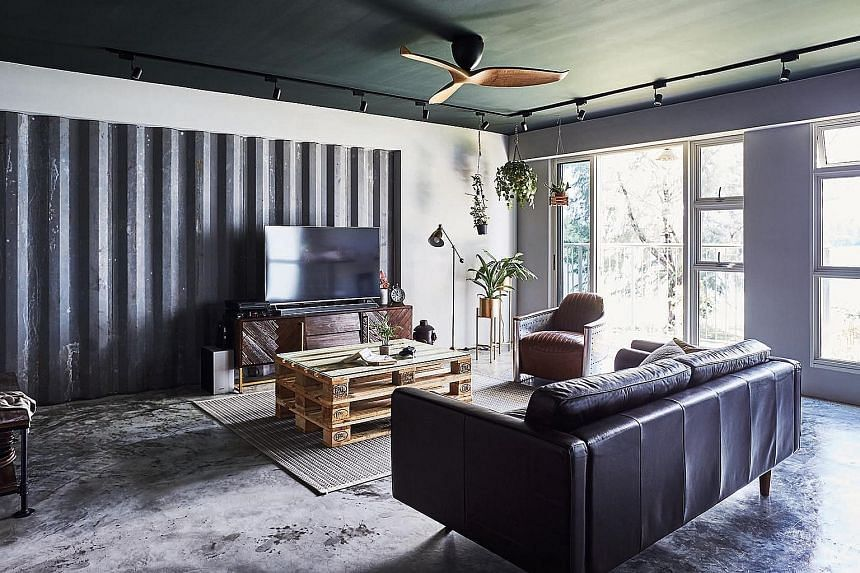 The home owners opted for a green study wall because they love plants and greenery. Corrugated galvanised iron sheets create striking backdrops in the kitchen and living room (above), while an armchair made from aeroplane fuselage complements the industri
