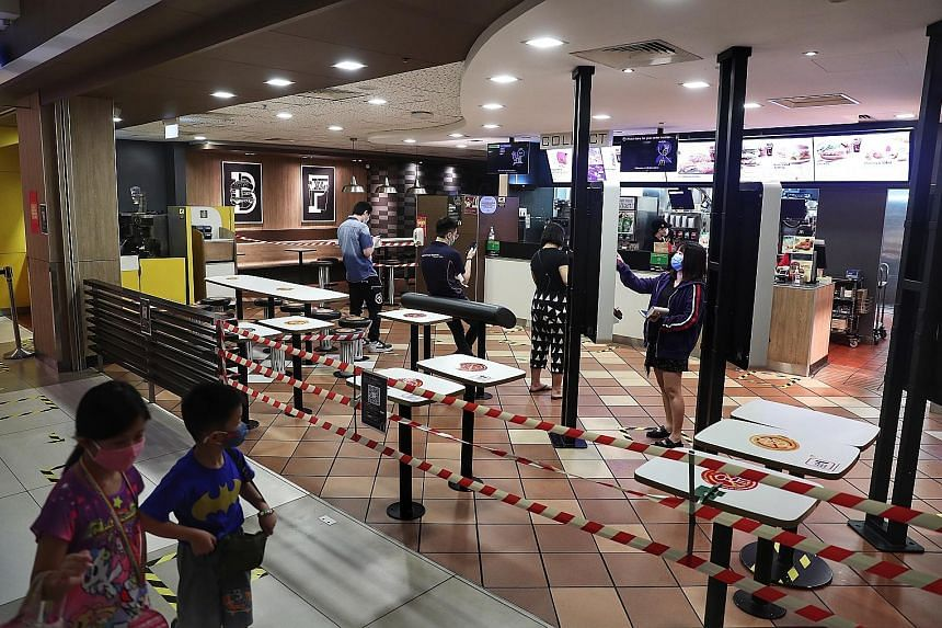 Customers at a McDonald's outlet at IMM yesterday. Given the restrictions that have been imposed, Singaporeans have been very resilient, and are complying with all the social distancing and circuit breaker rules, said President Halimah Yacob. ST PHOT