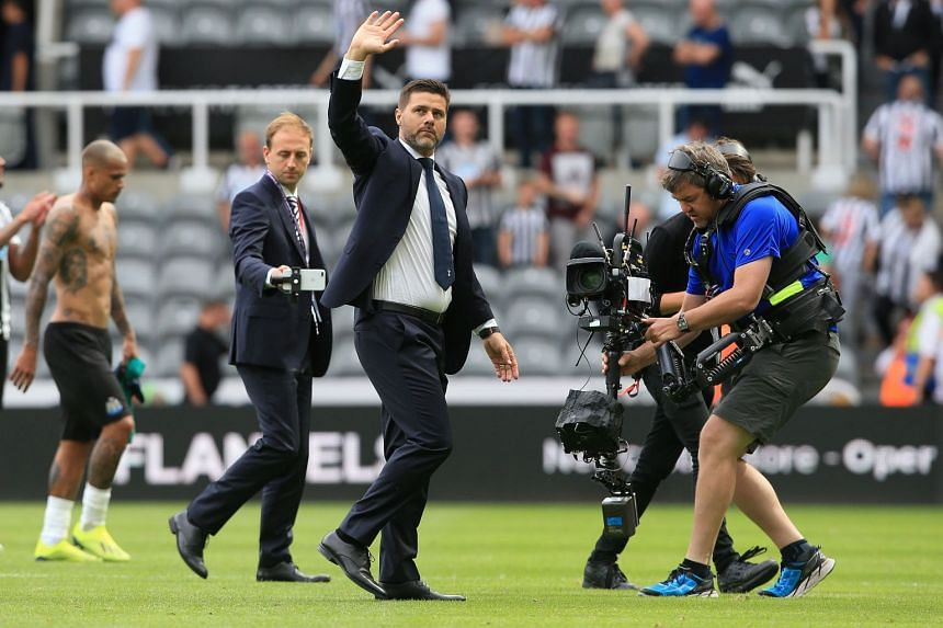 A 2018 photo shows Pochettino (centre) applauding fans after a match.