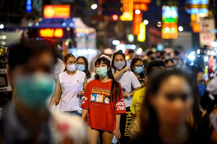 Pedestrians walk on the main street of Chinatown in Bangkok on May 21, 2020.