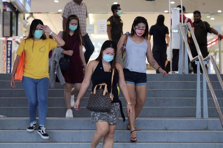 Foreign domestic workers exit from Lucky Plaza, Mar 29, 2020.