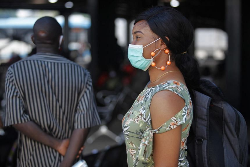 A woman wears a mask she waits for the bus in Lagos, Nigeria, on May 20, 2020.