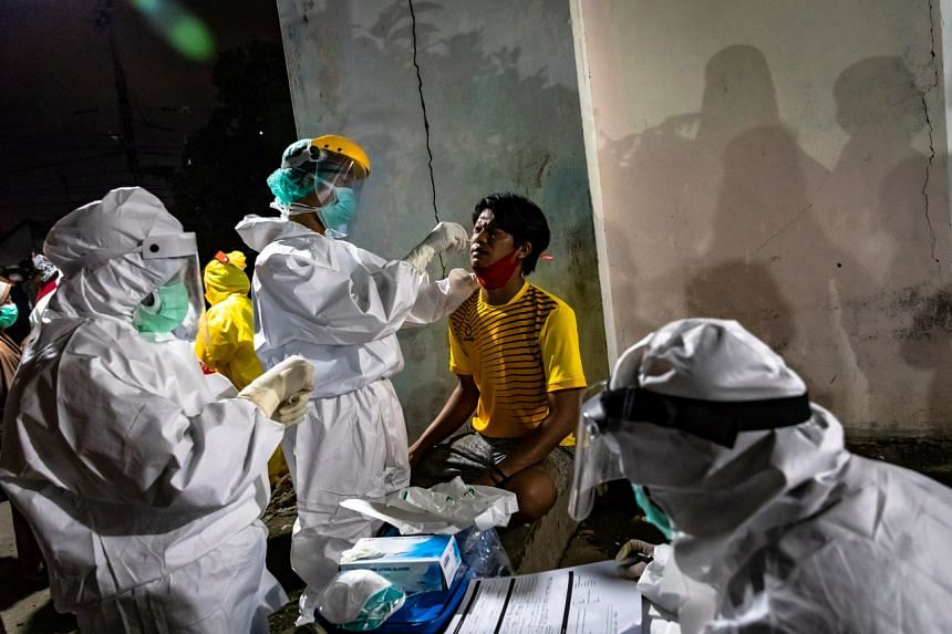 Medical staff take a swab sample from a vendor in Semarang, Indonesia on May 22, 2020.