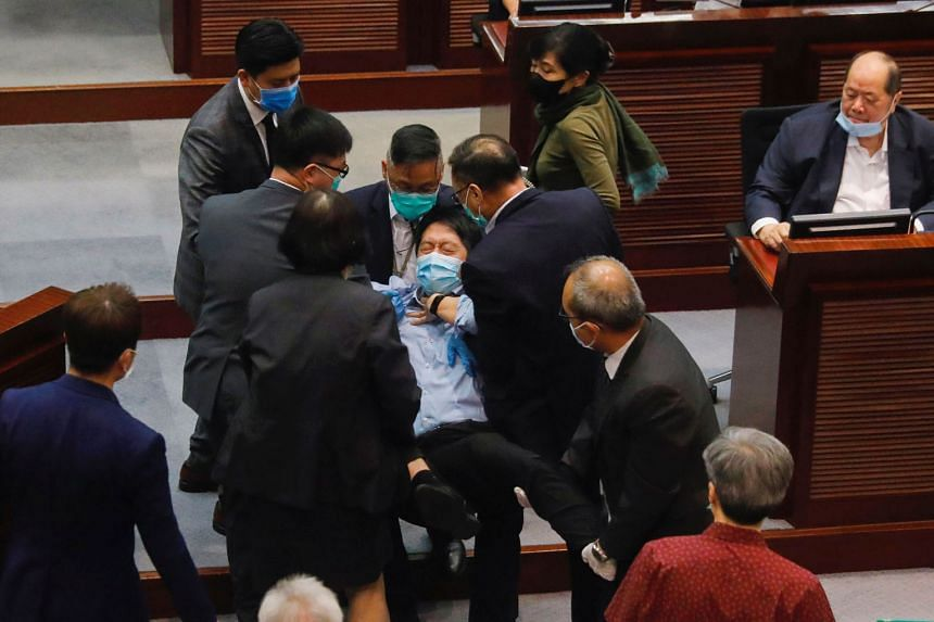 Pan-democratic legislator Hui Chi-fung being removed from a Legco meeting in Hong Kong yesterday, after he scuffled with security officers while protesting against Beijing's move to directly enforce a national security law. PHOTO: REUTERS