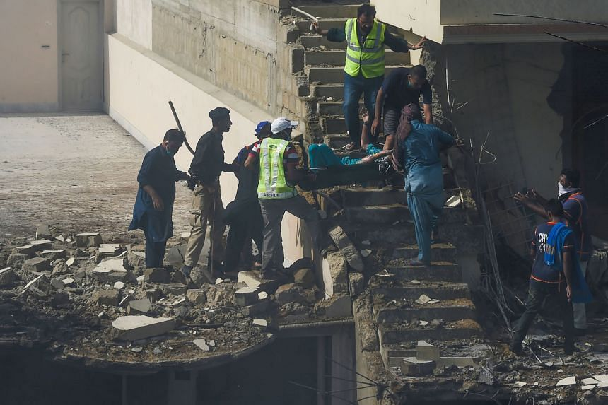 Above: An injured victim being evacuated by rescue workers from the site in a Karachi neighbourhood after a Pakistan International Airlines aircraft crashed into homes while on approach to the city's airport yesterday. There were no estimates of casu