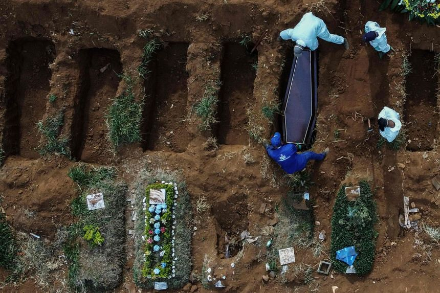 An aerial picture shows gravediggers burying an alleged Covid-19 victim at a cemetery in Sao Paulo, Brazil, on May 22, 2020.