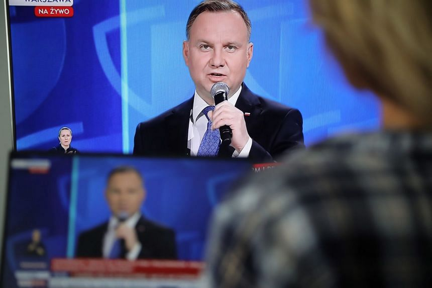A TV screen shows Polish President Andrzej Duda during a coronavirus press conference in Warsaw, May 19, 2020.