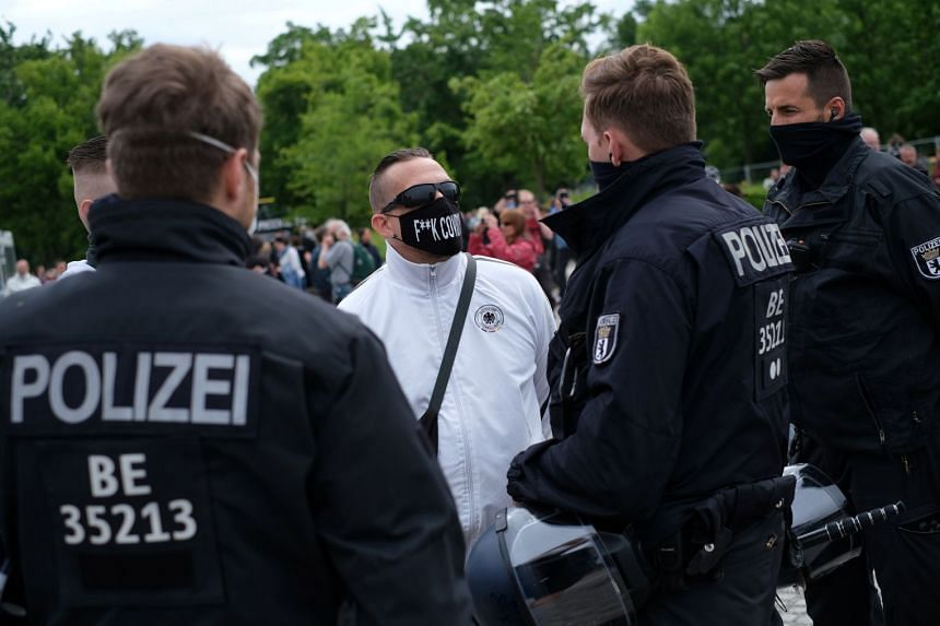 A man wearing a face mask speaks with police officers during a protest in Berlin, May 23, 2020.