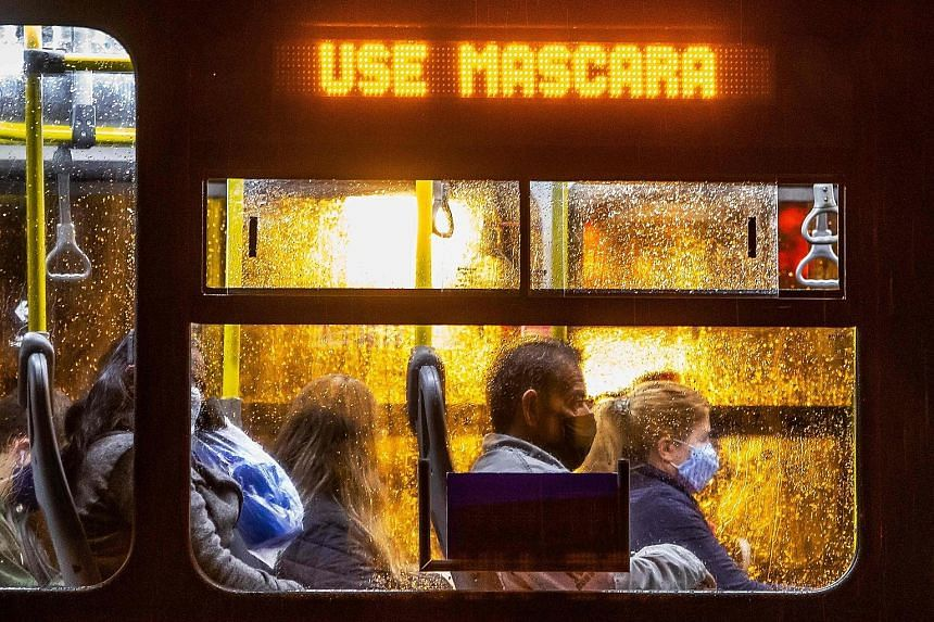 "Commuters wearing face masks on a public bus - with an electronic sign reading ""Wear a face mask"" - in Curitiba, Brazil, on Friday. Brazil confirmed that 330,890 people had been infected and registered 1,001 daily coronavirus deaths that day, taking"