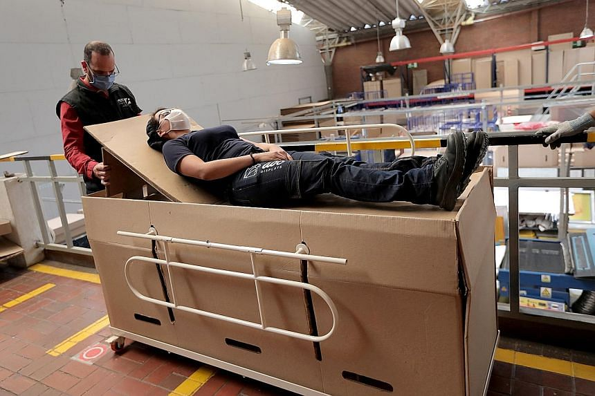 Manager Rodolfo Gomez showing how a hospital bed manufactured by his company can be transformed into a cardboard coffin, amid the Covid-19 outbreak in Bogota, Colombia, last Thursday.