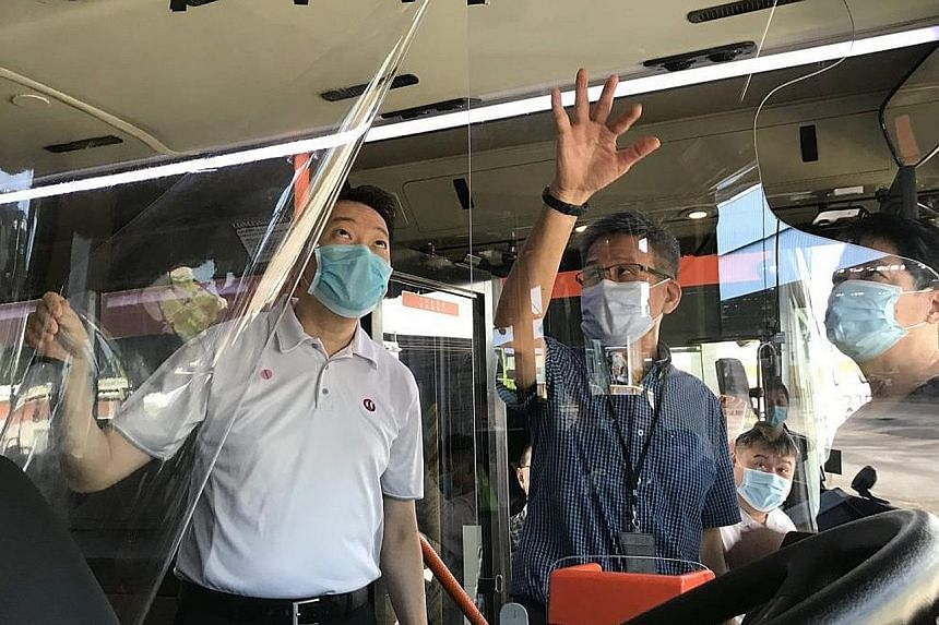 National Transport Workers' Union executive secretary Melvin Yong checking out a transparent shield that is being explored as a means to separate bus drivers from commuters. The union's other safe distancing measures include separators on tables at i