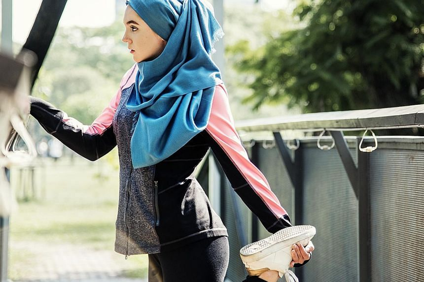 A Muslim woman stretching after a workout at the park. For some, faith and fitness intersect in the form of Ramadan boot camp workouts and Christian detox diets. PHOTO: ISTOCK