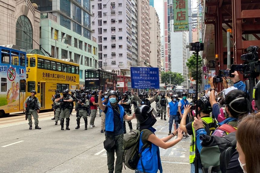 Hong Kong police officers unfurling a blue banner with a warning telling crowds to disperse, on May 24, 2020.