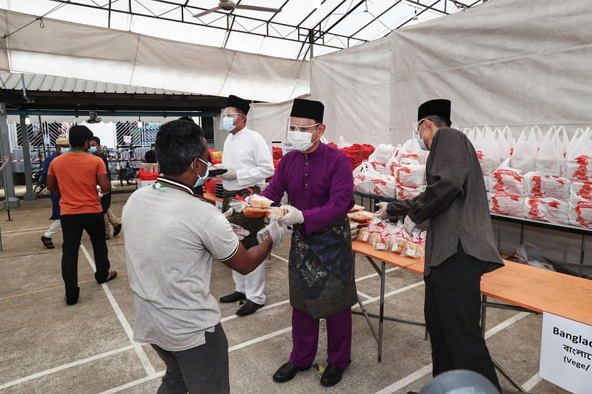 Minister of State for Manpower Zaqy Mohamad (centre), Muis chief executive Esa Masood (right) and SMCCI deputy president Abu Bakar Mohd Nor distributing the special meals andfestive goodies on May 24, 2020.