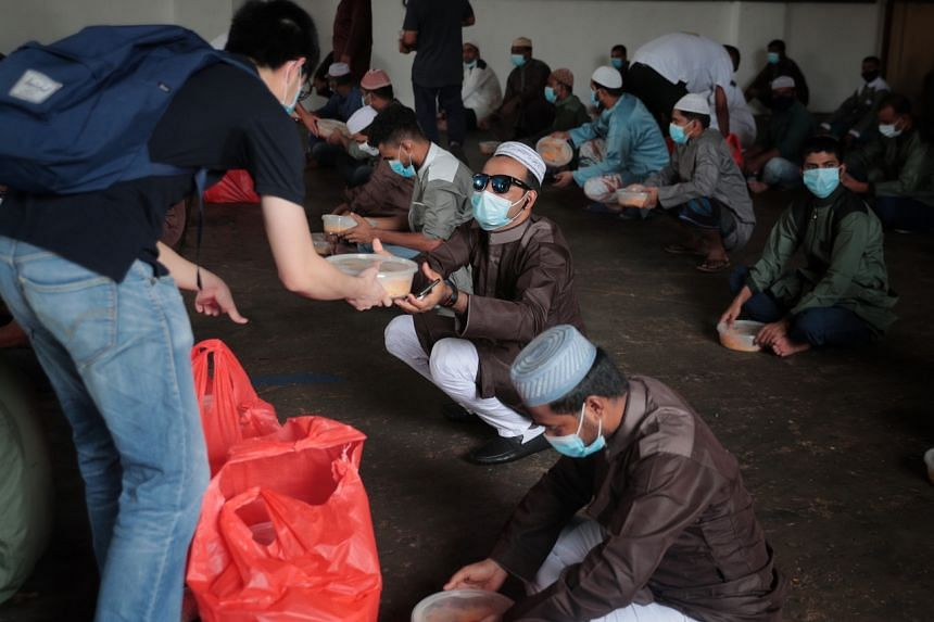 Migrant worker residents receiving their meal at a Hari Raya Puasa event at Chinsim dormitory on May 24, 2020.